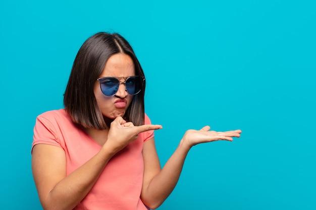 Jonge latijns-vrouw met zonnebril en wijst naar haar hand