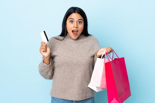 Jonge latijns-vrouw op blauwe muur boodschappentassen houden en verrast vrouw