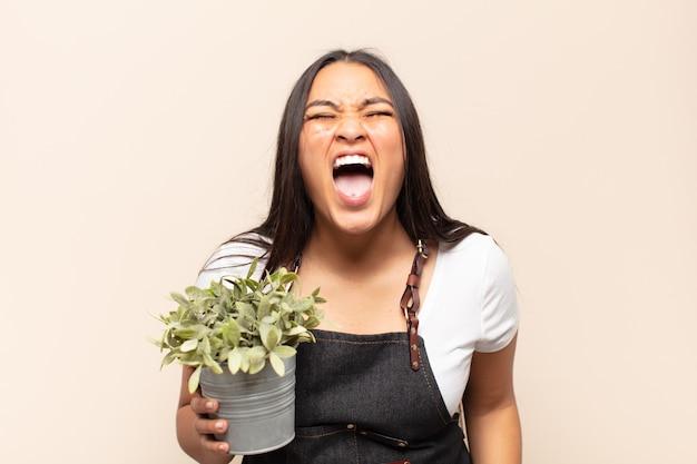 Jonge latijns-vrouw schreeuwt agressief, kijkt erg boos, gefrustreerd, verontwaardigd of geïrriteerd, schreeuwt nee