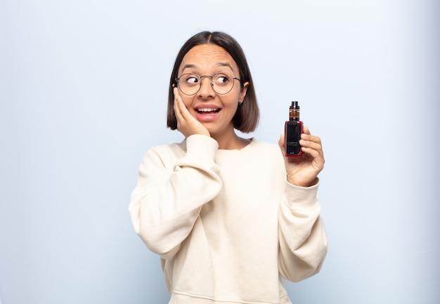 Jonge latijns-vrouw voelt zich blij, opgewonden en verrast, naar de zijkant kijkend met beide handen op het gezicht