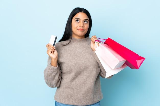 Jonge latijns-vrouw vrouw op blauwe muur houden boodschappentassen en een creditcard en denken