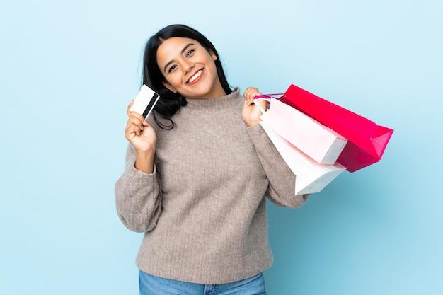 Jonge latijns-vrouw vrouw op blauwe muur met boodschappentassen en een creditcard