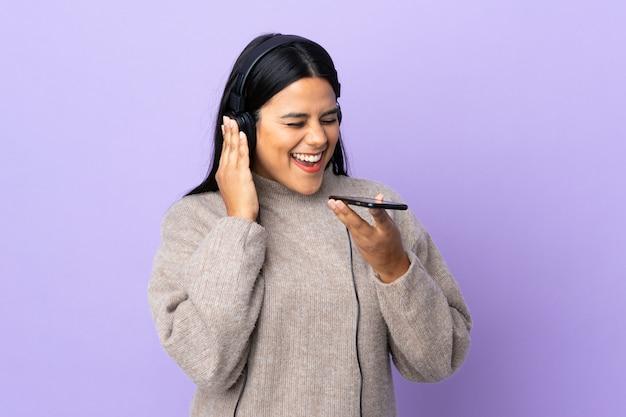 Jonge latijns-vrouw vrouw op paarse muur luisteren muziek met een mobiel en zingen