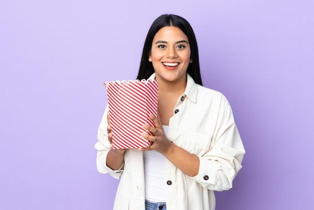 Jonge latijns-vrouw vrouw op witte muur met een grote emmer popcorns