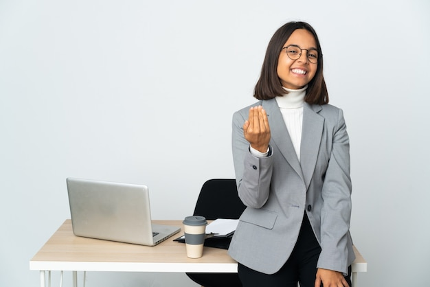 Jonge latijns-zakelijke vrouw die werkt in een kantoor geïsoleerd op een witte achtergrond die uitnodigt om met de hand te komen. blij dat je gekomen bent