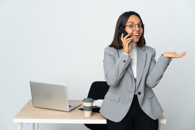 Jonge latijns-zakenvrouw die in een bureau werkt dat op witte achtergrond wordt geïsoleerd en een gesprek met de mobiele telefoon met iemand houdt