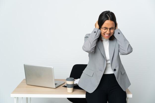 Jonge latijns-zakenvrouw die in een bureau werkt dat op witte gefrustreerde achtergrond wordt geïsoleerd en oren bedekt