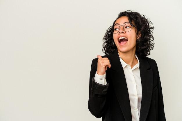 Jonge latijns-zakenvrouw geïsoleerd op een witte achtergrond wijst met duimvinger weg, lachend en zorgeloos.