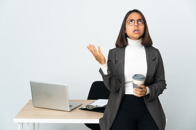 Jonge latijnse bedrijfsvrouw die in een bureau werkt dat op wit wordt geïsoleerd benadrukt onwhelmed