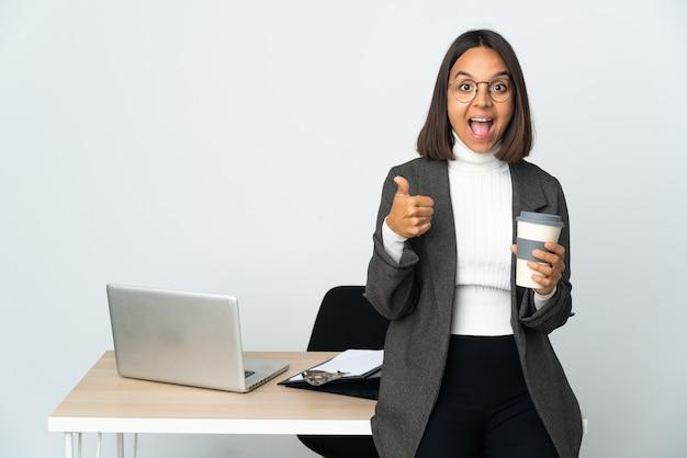 Jonge latijnse bedrijfsvrouw die in een bureau werkt dat op witte achtergrond wordt geïsoleerd die ok teken en duim omhoog gebaar toont