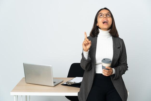 Jonge latijnse bedrijfsvrouw die in een bureau werkt dat op witte achtergrond wordt geïsoleerd die verrast en benadrukt