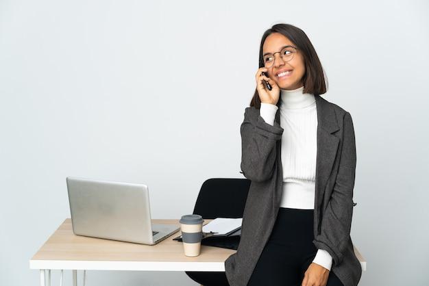 Jonge latijnse bedrijfsvrouw die in een bureau werkt dat op witte muur wordt geïsoleerd die een gesprek met de mobiele telefoon houdt