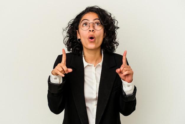 Jonge latijnse bedrijfsvrouw die op witte achtergrond wordt geïsoleerd die met geopende mond ondersteboven richt.