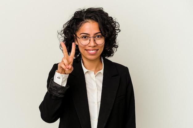 Jonge latijnse bedrijfsvrouw die op witte achtergrond wordt geïsoleerd die nummer twee met vingers toont.