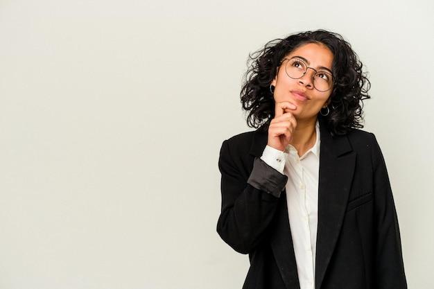 Jonge latijnse bedrijfsvrouw die op witte achtergrond wordt geïsoleerd die zijwaarts met twijfelachtige en sceptische uitdrukking kijkt.