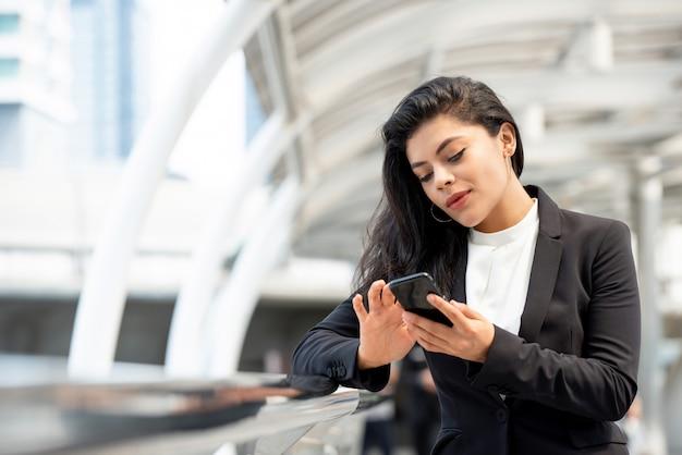 Jonge latijnse bedrijfsvrouw die smartphone in openlucht gebruiken