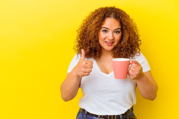 Jonge latijnse bochtige vrouw die een kop houdt die op gele muur wordt geïsoleerd die en duim glimlacht opheft