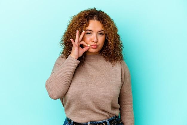 Jonge latijnse bochtige vrouw die op blauwe achtergrond met vingers op lippen wordt geïsoleerd die een geheim houden.