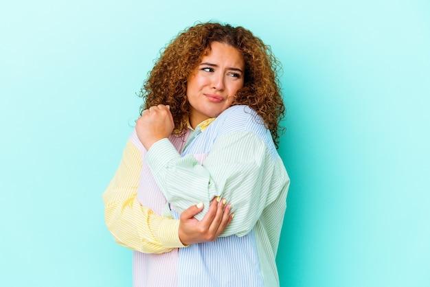 Jonge latijnse bochtige vrouw die op blauwe achtergrond verward wordt geïsoleerd, voelt twijfelachtig en onzeker.