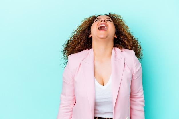 Jonge latijnse bochtige vrouw die op blauwe muur wordt geïsoleerd die zeer boos, gefrustreerd woedeconcept schreeuwt.