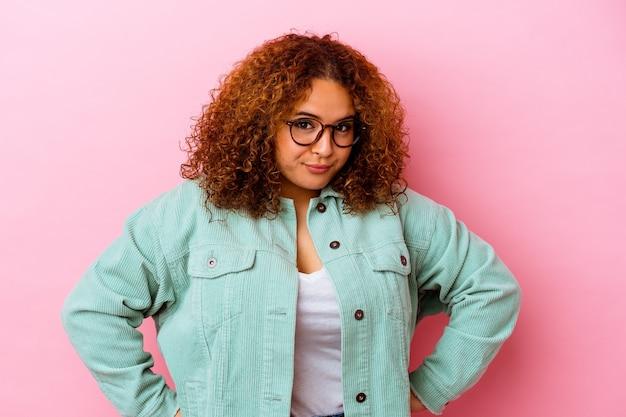Jonge latijnse bochtige vrouw die op roze achtergrond wordt geïsoleerd die verward, twijfelachtig en onzeker voelt.