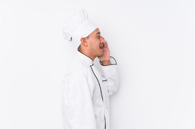 Jonge latijnse chef-kokmens die en palm schreeuwen houden dichtbij open mond.