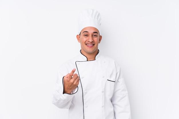 Jonge latijnse chef-kokmens die met vinger op u richt