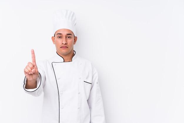 Jonge latijnse geïsoleerde chef-kokmens die nummer één met vinger toont.
