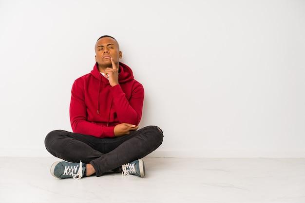 Jonge latijnse geïsoleerde mensenzitting op de vloer zijdelings het kijken met twijfelachtige en sceptische uitdrukking.