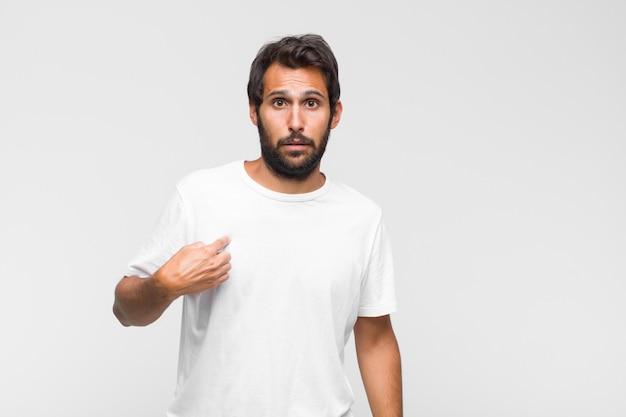 Jonge latijnse knappe man die gezicht bedekt met beide handen en zegt nee tegen de camera! afbeeldingen weigeren of foto's verbieden