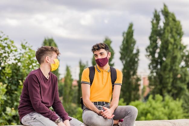Jonge latijnse man en spaanse transgendervrienden tijdens het nieuwe normale gezichtsmasker voor sociale afstand