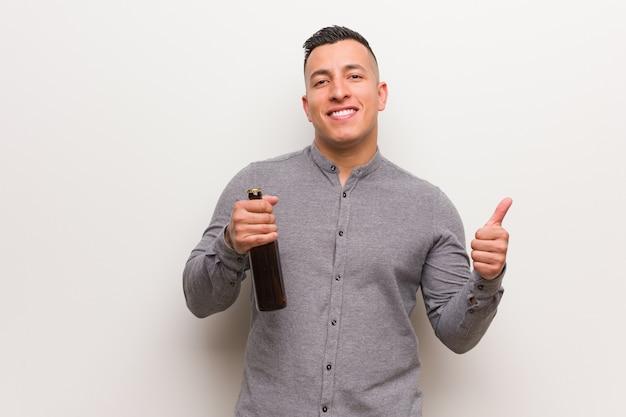 Jonge latijnse mens die een bier houdt dat en duim opheft