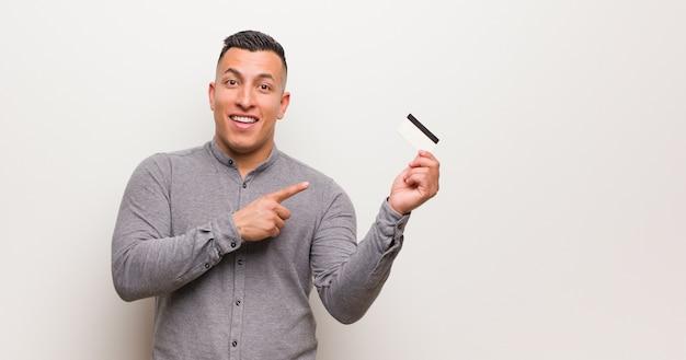 Jonge latijnse mens die een creditcard houdt die aan de kant met vinger richt