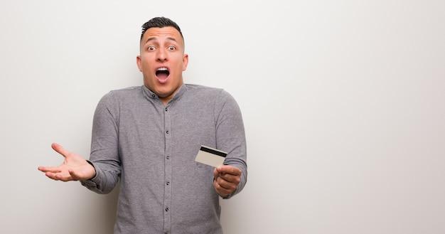 Jonge latijnse mens die een creditcard houdt die een overwinning of een succes viert