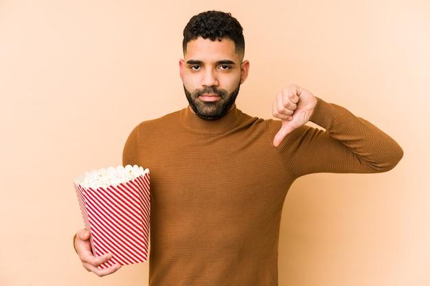 Jonge latijnse mens die een geïsoleerde pop corn houdt met een afkeergebaar, duimen naar beneden. meningsverschil concept.