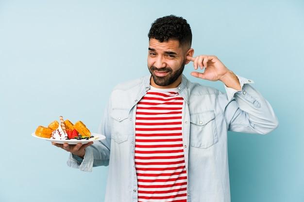 Jonge latijnse mens die een geïsoleerde wafel houdt die oren behandelt met handen.