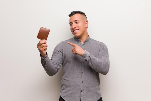 Jonge latijnse mens die een portefeuille houdt die aan de kant met vinger richt