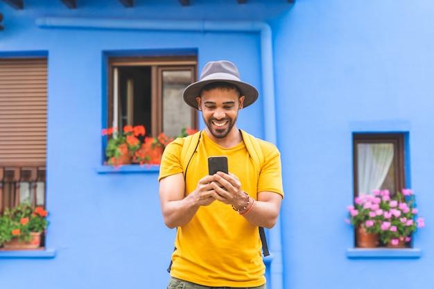 Jonge latijnse mens die het glimlachen cellphone gebruikt.