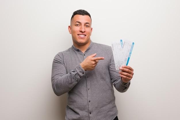 Jonge latijnse mens die luchtkaartjes houden die kant met vinger richten