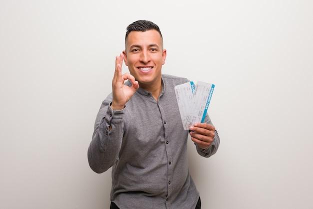 Jonge latijnse mens die luchtkaartjes houdt vrolijk en zeker doend ok gebaar