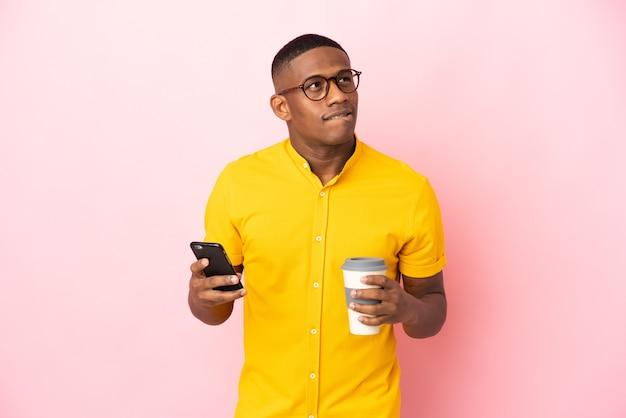 Jonge latijnse mens die op roze muur wordt geïsoleerd die koffie houdt om mee te nemen en een mobiel terwijl hij iets denkt
