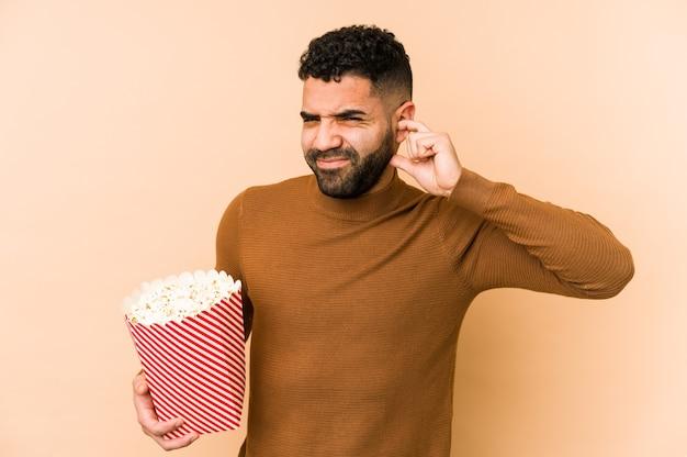 Jonge latijnse mens die pop corn geïsoleerd houdt die oren behandelt met handen.