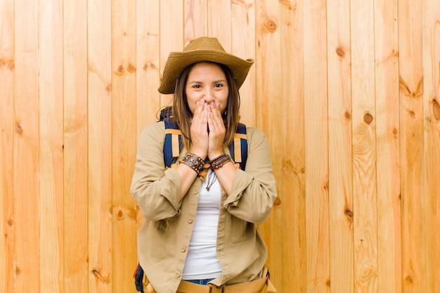 Jonge latijnse ontdekkingsreizigervrouw tegen houten muur