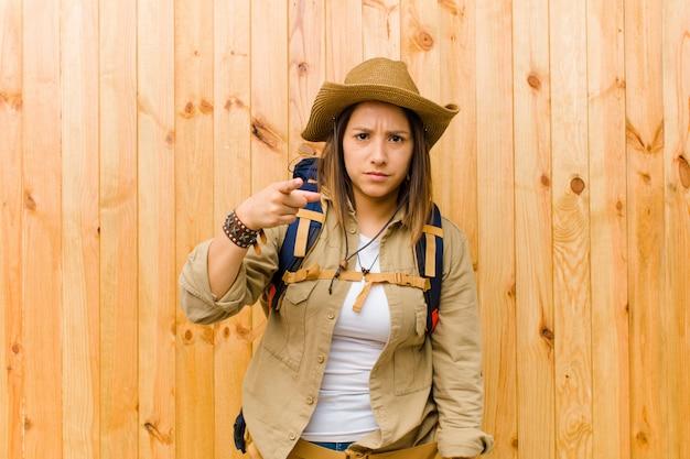 Jonge latijnse ontdekkingsreizigervrouw tegen houten muurachtergrond