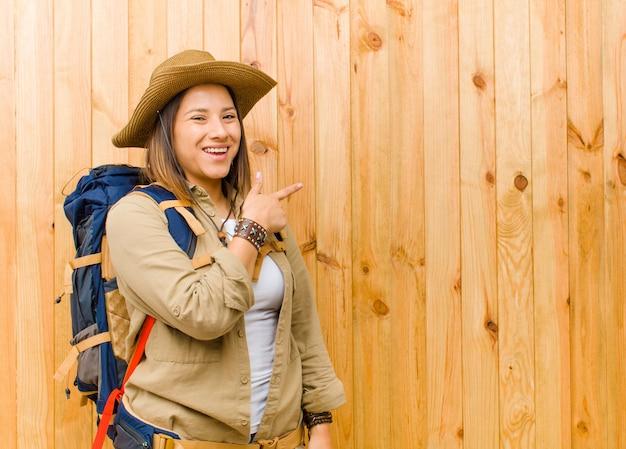 Jonge latijnse ontdekkingsreizigervrouw tegen houten