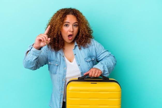 Jonge latijnse reiziger bochtige vrouw die een koffer houdt die op blauwe achtergrond wordt geïsoleerd die een idee, inspiratieconcept heeft.