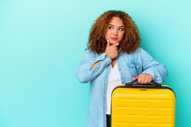 Jonge latijnse reiziger bochtige vrouw die een koffer houdt die op blauwe achtergrond wordt geïsoleerd die zijwaarts kijkt met twijfelachtige en sceptische uitdrukking.