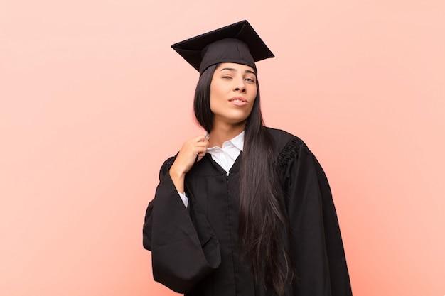 Jonge latijnse studente die beklemtoond, bezorgd, vermoeid en gefrustreerd voelt, overhemdshals trekt, gefrustreerd met probleem kijkt