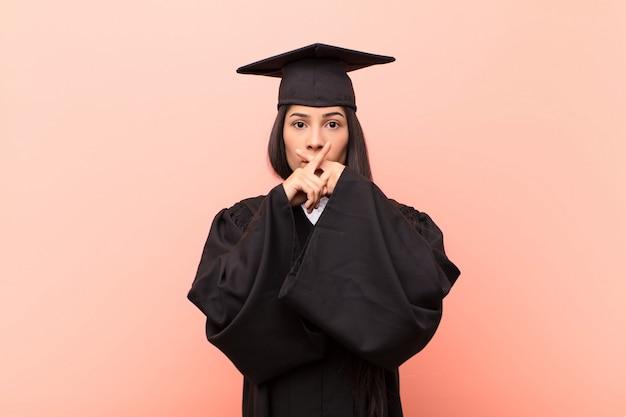 Jonge latijnse studente die ernstig en ontevreden kijkt met beide vingers van voren gekruist in afwijzing, vragend om stilte
