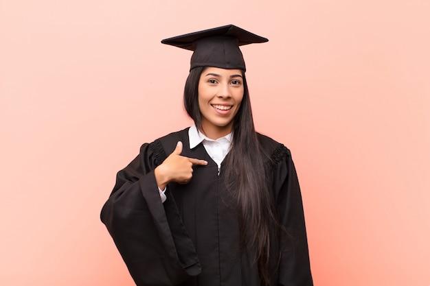 Jonge latijnse studente die gelukkig, trots en verrast kijkt, opgewekt naar zichzelf wijst, zelfverzekerd en verheven voelt